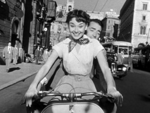 Audrey_Hepburn_and_Gregory_Peck_on_Vespa_in_Roman_Holiday_trailer